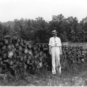 County agent in front of shortleaf pine billets