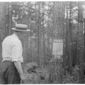 County agent with forestry poster