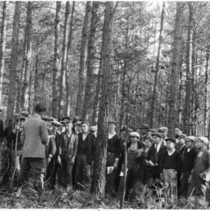 C. G. Kirkman and agricultural students studying farm timber