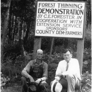 C. E. Forester and Agent K. A. Haney in front of sign notifying forest thinning demonstration