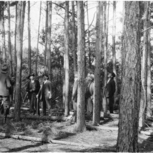 Agent N. C. Shiver with farmers studying thinned loblolly pine