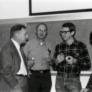 Five men in front of blackboard