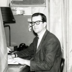 """Dr. Leroy C. """"Bud"""" Saylor at desk"""