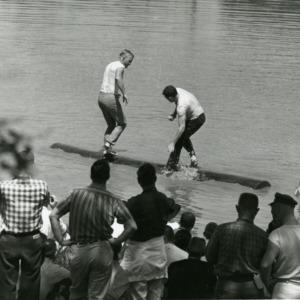 Two men balancing on log