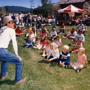Man in cowboy hat with crowd of children and adults