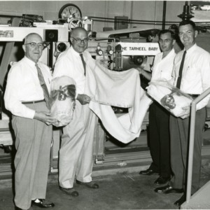 Four men in front of The Tarheel Baby machine