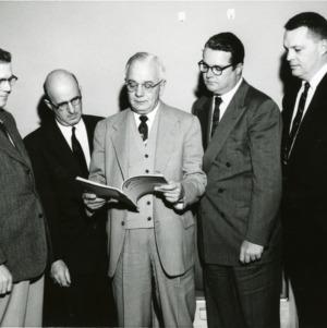 Five men looking at booklet