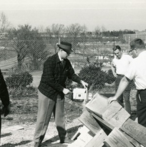 Bill Huxter with chainsaw, John Gray, and two other men
