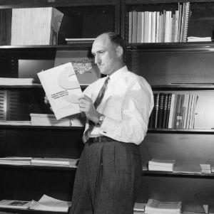 Charles E. Bishop examining book