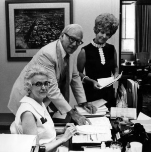 John T. Caldwell and two women at desk