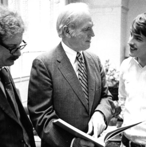 John T. Caldwell examining book with two others