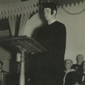 William C. Friday in graduation robes at podium