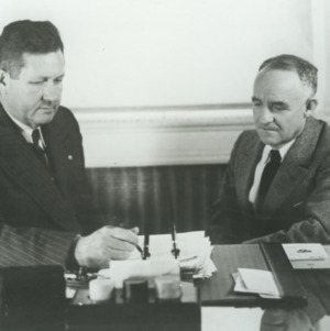 John W. Harrleson and Frank P. Graham at desk