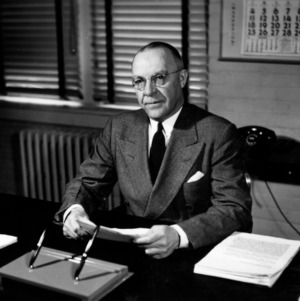 Dean James H. Hilton at desk