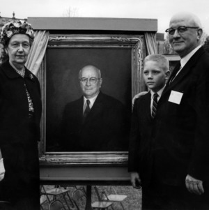 Rose Lampe, Dean J. Harold Lampe, and their grandson at the unveiling of Dean Lampe's portrait