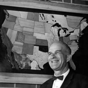 Dean Richard J. Preston with map made of wood carvings