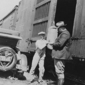 W. Kerr Scott and other unloading car of fish meal at train depot