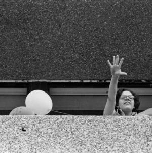 Mary Beth Spina waving from balcony