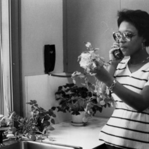 Female student on phone, with plants