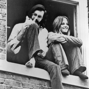 Two students sitting on window sill with cat