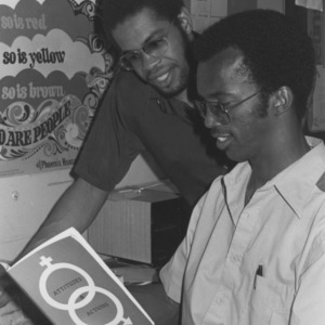 Two students looking at book