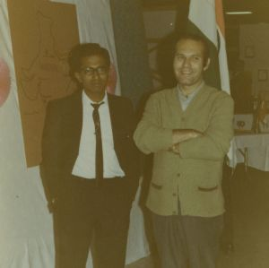 Two men in front of India booth at international fair