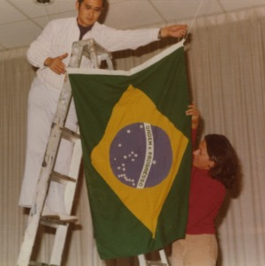 People hanging flag at Brazil booth at international fair