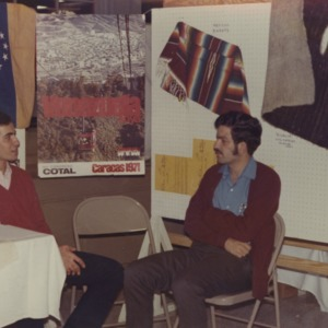 Two men at Venezuela booth at international fair