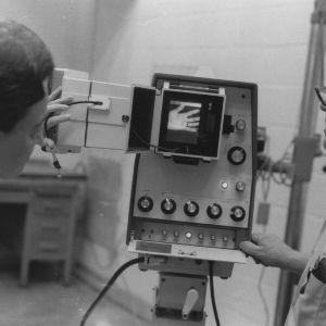 Two men examining lab machinery