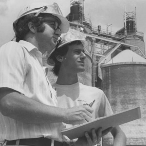 Two men in hardhats outside scientific facility