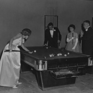 Students in fancy dress playing pool