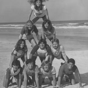 Students making human pyramid on beach