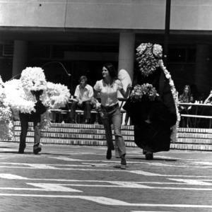 Woman being chased by people in bug costumes