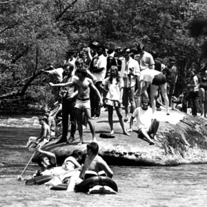 Group of students on large river rock during Neuse River Derby