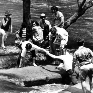 People gathered on river rocks during Neuse River Derby