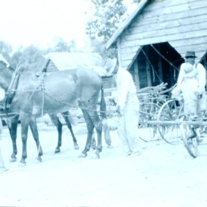 A group of four people hooking up a horse and cart at a barn
