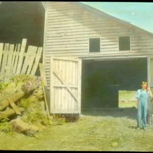 Boy standing in front of a barn