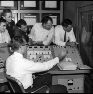 Six men with nuclear reactor control equipment