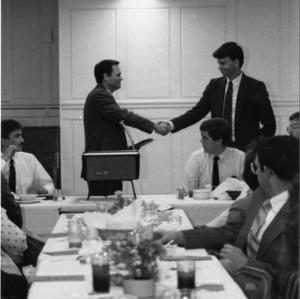 Men shaking hands at dinner