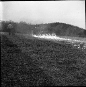 Man with agricultural machinery and fire in field