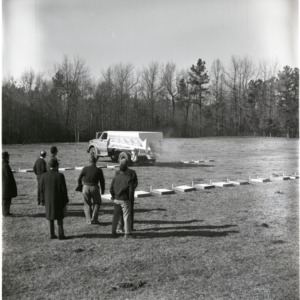 Men observing fertilizer spreader calibration