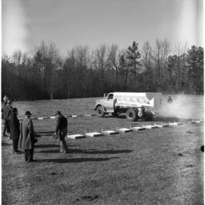 Men observing fertilizer spreader calibration