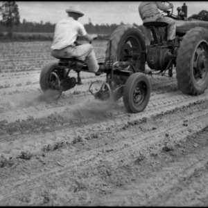 Two men operating tractor