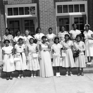 Group portrait of African American Women 4-H Leaders, one in a gown, at A & T College, 1951