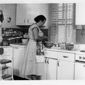 Demonstration agent in kitchen of African American demonstration home, 1956