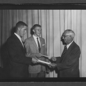 Dean I. O. Schaub presenting award to students