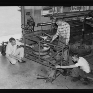 1959 Engineers Fair: Information Booth, inertia car, and girl standing in pipe